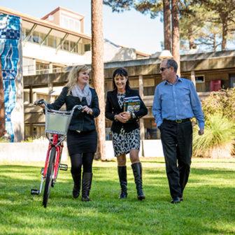 Three staff members walking on grass through campus